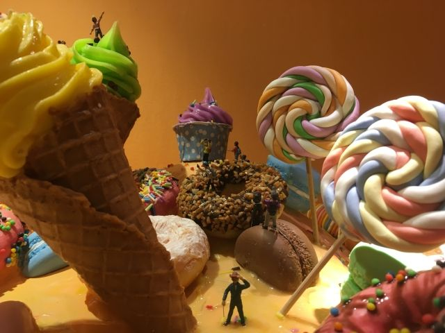 Tiny models of people are dwarfed by what looks like giant lollypops and ice creams at Wonderfood Museum Penang
